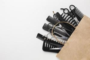 Haarwerkzeugsatz in Papiertüte auf weißem Hintergrund foto