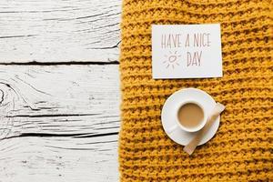 haben eine schöne Tagesnachricht mit Tasse Kaffee und gelber Decke auf hölzernem Hintergrund foto