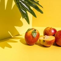 Vorderansicht von hellen Pfirsichen mit harten Schatten auf dynamischem gelbem Hintergrund foto