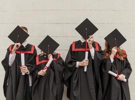 Vorderansicht von Absolventen, die Gesichter bedecken foto