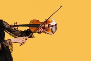 Mädchen, das Geige auf gelbem Hintergrund spielt foto