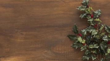 grüne Stechpalmenzweige auf braunem Tisch foto
