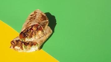 Hochwinkelanordnung mit Burrito und grünem und gelbem Kopierraum foto