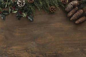 Stechpalmenzweige mit Zapfen auf Holztisch foto