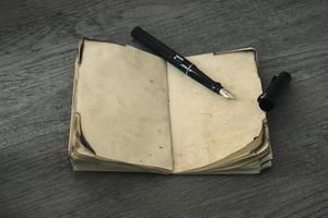 Tintenstift mit einem alten Notizbuch geöffnet foto