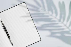 Kopieren Sie Raum Notizbuch mit Blättern Schatten foto