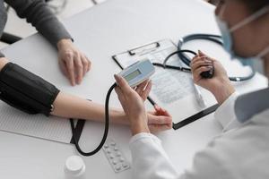 Arzt prüft den Gesundheitszustand des Patienten foto
