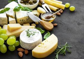 verschiedene Arten von Käse, Trauben, Honig und Snacks foto