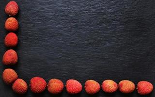 Litschis auf Schieferhintergrund für Menüs, Etiketten oder Schilder foto