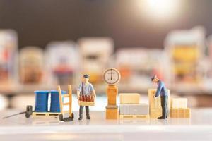 Miniaturleute, diensthabende Postboten, die sich darauf vorbereiten, dem Verbraucher eine Schachtel zu schicken. Lieferservice für E-Commerce-Konzept foto
