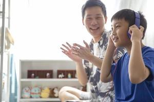 glückliche Familie, während Sie Kopfhörer verwenden, um Musik zu hören und zu lächeln, genießen Sie die Zeit zusammen zu Hause foto