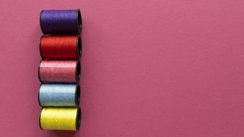 violette, rote, rosa, blaue, gelbe Farben Garnrollen auf pastellfarbenem Texturhintergrund. flach lag mit Kopierraum. Foto auf Lager.