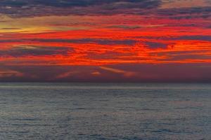 bunter roter Sonnenuntergang über einem Gewässer foto