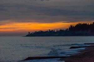 bunter roter Sonnenuntergang über einem Gewässer neben einer Küste in abkhazia foto