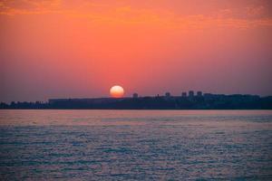 bunter roter Sonnenuntergang über einem Gewässer und Stadtbild in Sukhumi, Abkhazia foto