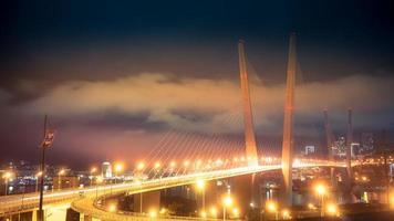 beleuchtete goldene Brücke mit bewölktem Himmel in der Nacht in Wladiwostok, Russland foto