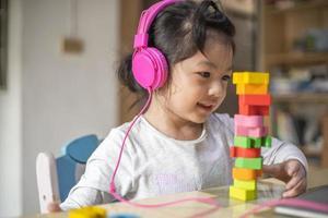 asiatisches Mädchen, das mit Kopfhörern und Laptop lernt, glückliches Mädchen, das online mit Laptop zu Hause lernt. foto