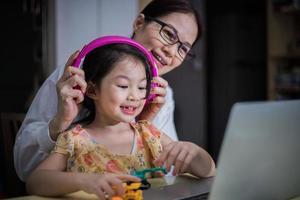Eine Mutter setzt ihrer Tochter Kopfhörer auf, um sie beim Online-Lernen zu unterstützen. foto