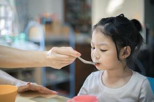 Ein kleines Mädchen isst etwas von einem Löffel. foto