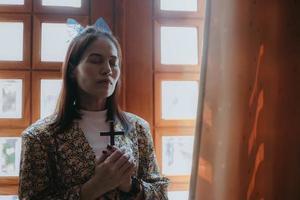 Eine Frau betet und hält ein Kreuz foto
