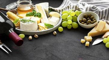 Käse, Trauben, Wein und Snacks foto