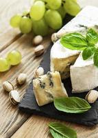 verschiedene Arten von Käse, Trauben und Nüssen foto