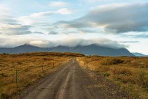 Schotterstraße über ein herbstfarbenes Feld in Island foto