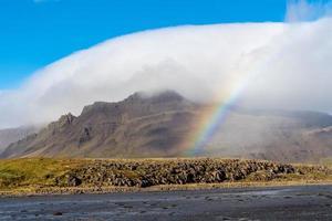 Berg bedeckt in einer weißen Wolke mit einem Regenbogen foto