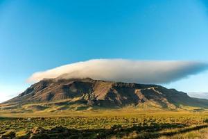Berg mit einer weißen Wolke, die über der Spitze schwimmt foto