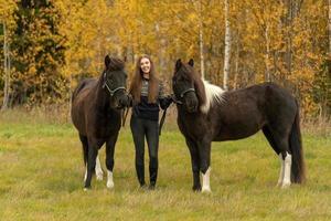 junge schwedische Frau in einem herbstfarbenen Feld mit ihren zwei isländischen Pferden foto