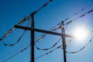 Turm mit Hochspannungsleitungen bei strahlendem Sonnenschein foto
