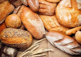 Haufen verschiedener Brote mit Weizenähren foto