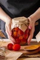junge Frau, die ein Glas eingelegtes Gemüse hält. Fermentationsprozess von Tomaten. gesundes Öko-Essen. foto