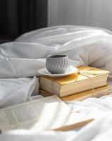 Anordnung mit Büchern und Tasse im Bett foto