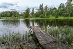 alter schräger hölzerner Pier in einem kleinen See foto