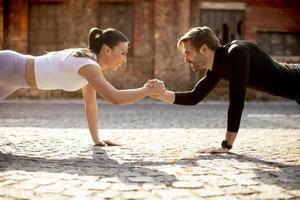 hübsches junges Paar, das einarmige Liegestützübungen in der städtischen Umgebung macht foto