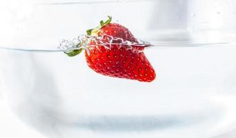 Erdbeere schwimmt im Wasser foto
