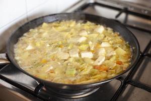 Tofu mit Gemüse in einer Pfanne, die gekocht wird foto