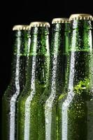 Bier in grünen Flaschen auf schwarzem Hintergrund foto