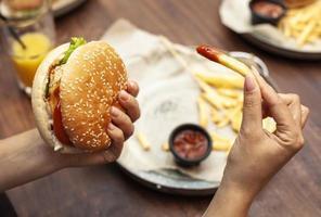 High Angle Person, die einen Burger und Pommes frites isst foto