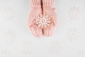 menschliche Hände tragen Fäustlinge mit rosa Papierschneeflocken foto