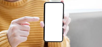 Person in einem gelben Pullover, der ein Telefon hält foto