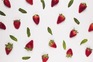 helle saftige Erdbeeren mit grünen Blättern auf weißem Hintergrund foto