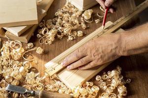 Zimmermann arbeitet mit Bleistift an einem Stück Holz foto