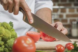 Chefkoch schneidet Tomate mit scharfem Messer an Bord foto