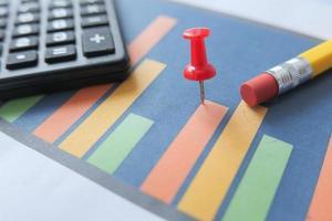 Finanzdiagramm mit Taschenrechner und Notizblock auf dem Tisch foto