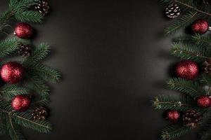 Weihnachtszusammensetzung von grünen Tannenzweigen mit roten Kugeln foto