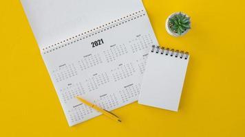 Flat Lay 2021 Kalender mit Kopierraum und Notizblock auf gelbem Hintergrund foto