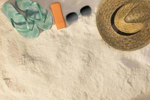 Hut und Sonnenbrille mit blauen Sandalen und Sonnencreme auf Strandsand foto