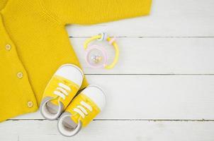 flach lag gelbe Babykleidung mit hölzernem Hintergrund foto